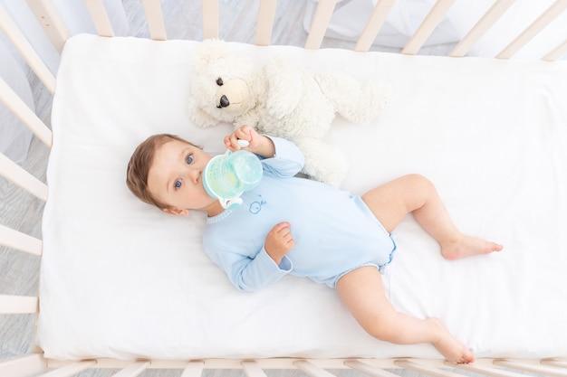 Dziecko z butelką mleka w rękach w łóżeczku jedzenie, koncepcja żywności dla niemowląt