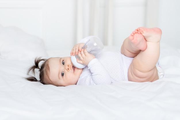 Dziecko z butelką na łóżku w domu, koncepcja jedzenia dla niemowląt