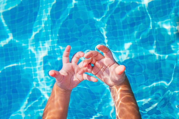 Dziecko z ciekawością obserwuje ręce zanurzone w wodzie basenu.