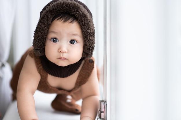 Dziecko z ciekawością szuka czegoś przy białym oknie