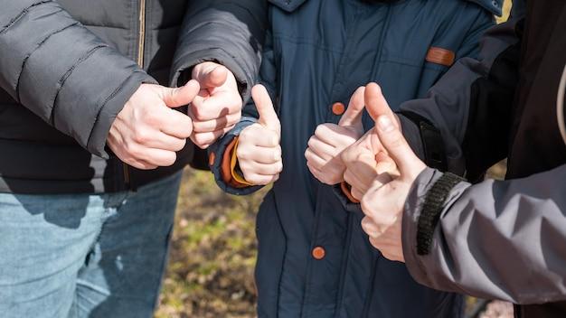 Dziecko z dwóch mężczyzn wyświetlono kciuk do góry znak, koncepcja zespołu