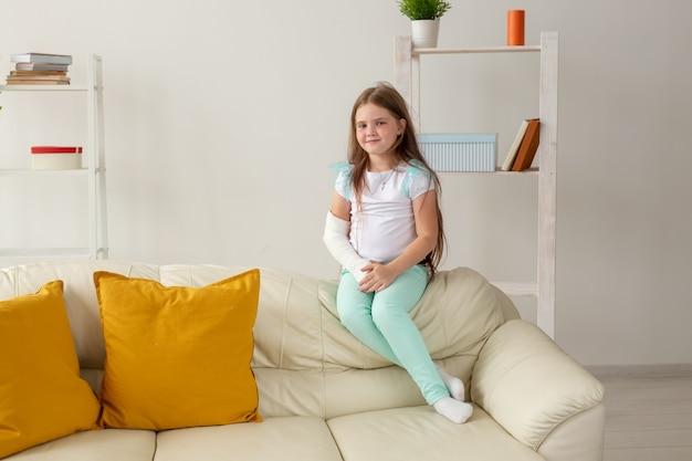 Dziecko z gipsem na złamanym nadgarstku lub ramieniu uśmiecha się i bawi się na kanapie. pozytywne nastawienie
