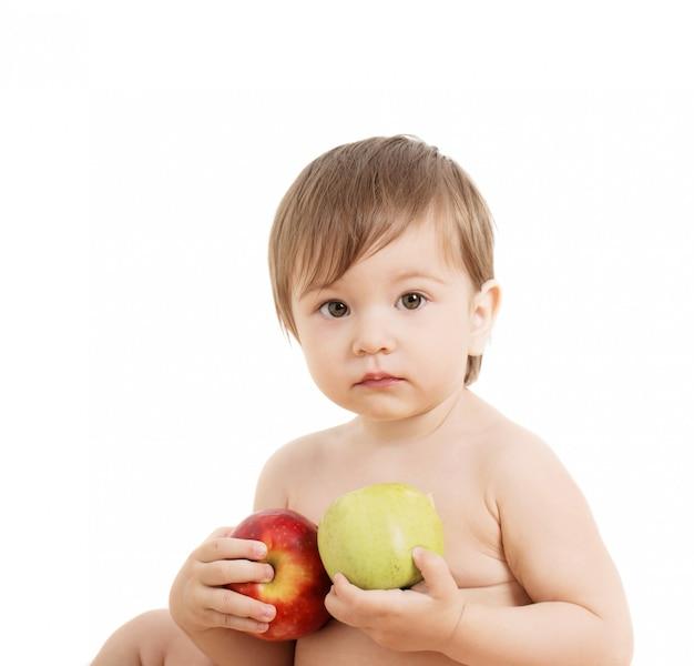 Dziecko z jabłkami na białym tle