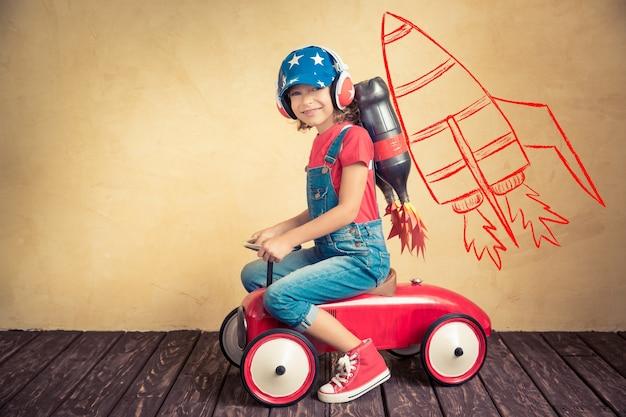 Dziecko z jet packiem jazdy retro autko. dziecko bawiące się w domu. koncepcja sukcesu, lidera i zwycięzcy