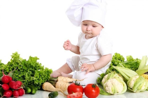 Dziecko z kapeluszowym szefem kuchni otoczonym warzywami