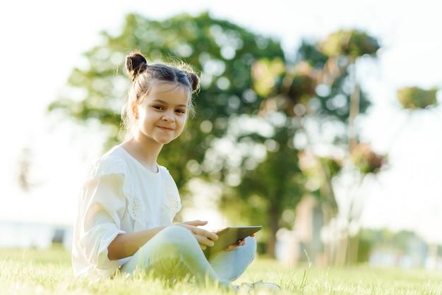 Dziecko z komputera typu tablet na zewnątrz. mała dziewczynka na trawie z komputerem