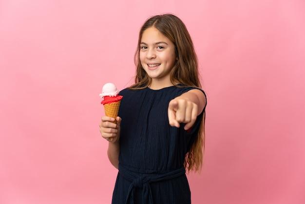 Dziecko z lodami cornet na białym tle różowy wskazując przód z szczęśliwym wyrazem twarzy