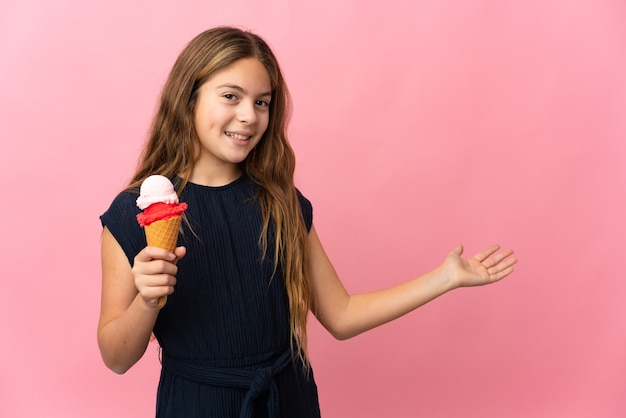 Dziecko z lodami kornetkowymi na białym tle różowym wyciągając ręce na bok za zaproszenie do przyjścia