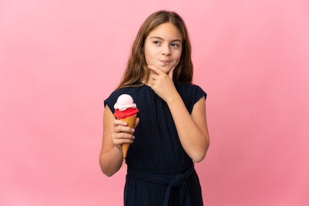 Dziecko z lodami kornetkowymi na na białym tle różowy ma wątpliwości