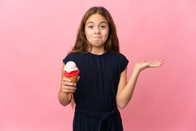 Dziecko z lodami kornetkowymi na na białym tle różowym tle, mając wątpliwości podczas podnoszenia rąk