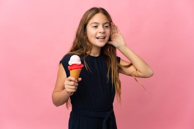 Dziecko z lodami kornetkowymi na pojedyncze różowe ściany, słuchając czegoś, kładąc rękę na uchu