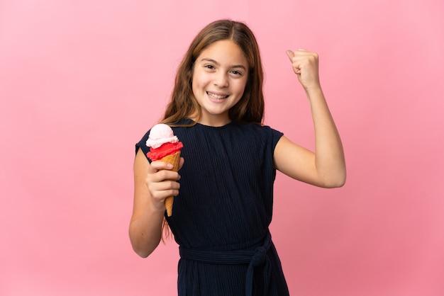 Dziecko z lodami kornetowymi na na białym tle różowym tle świętuje zwycięstwo