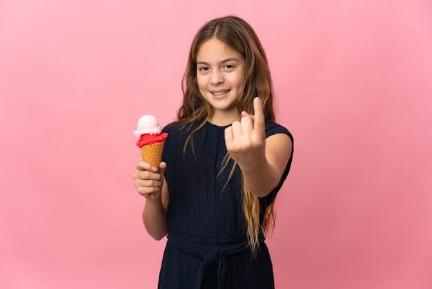 Dziecko z lodami kornetowymi nad odizolowaną różową ścianą robi nadchodzący gest
