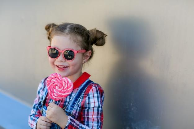 Dziecko z lollipopem na patyku w rękach na tle ściany