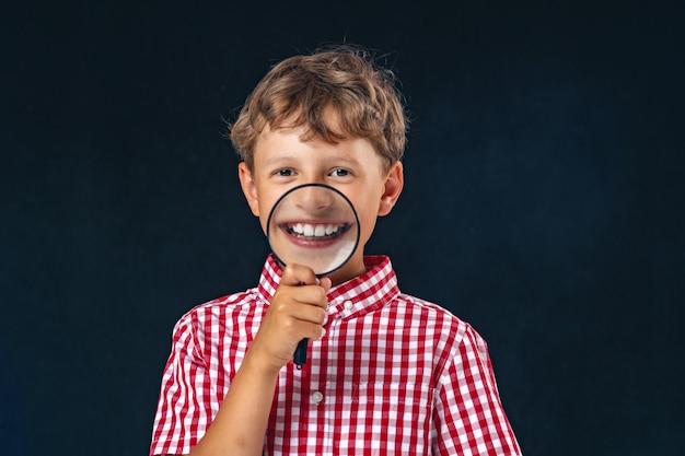 Dziecko z lupą w pobliżu ust na białym tle