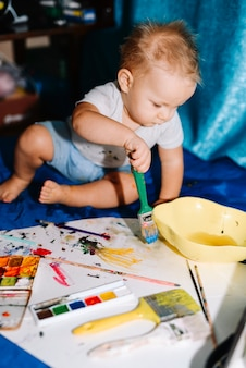 Dziecko z malowania pędzlem na papierze w pobliżu kolorów wody i siedzi na narzuty