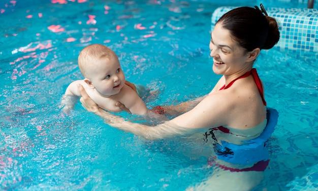 Dziecko z mamą uczy się pływać w basenie