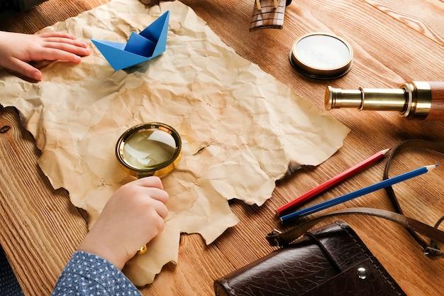 Dziecko z mapą i lupą przy stole.