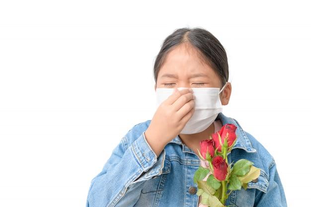Dziecko z maską, aby zapobiec alergii i trzyma czerwoną różę