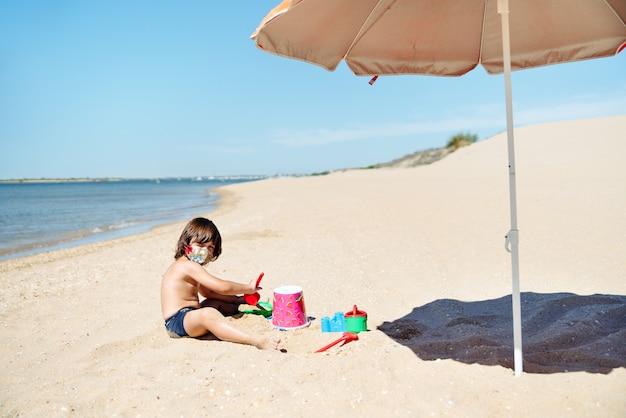 Dziecko z maską na twarzy na wakacjach bawi się zabawkami na piasku plaży obok pomarańczowego parasola w środku pandemii koronawirusa