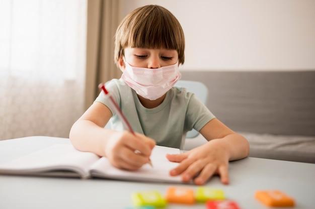 Dziecko z medyczną maską pisze przy biurkiem