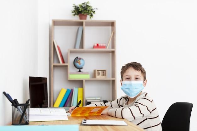 Dziecko z medyczną maską pozuje podczas gdy odrabiający pracę domową