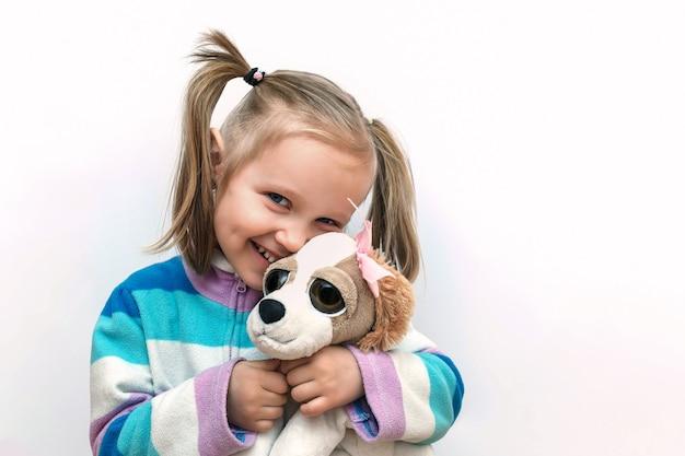 Dziecko z miękką zabawką mała blond dziewczynka obejmuje szczeniaka