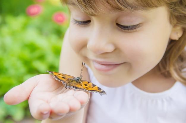 Dziecko z motylem. idea leuconoe. selektywne skupienie.
