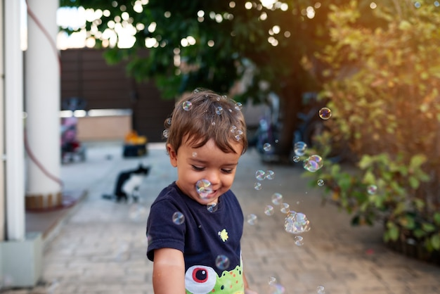 Dziecko z niebieską koszulką bawi się bańkami mydlanymi