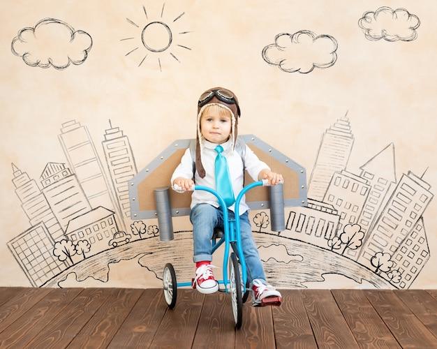 Dziecko z papierowymi skrzydłami, grając w pomieszczeniu