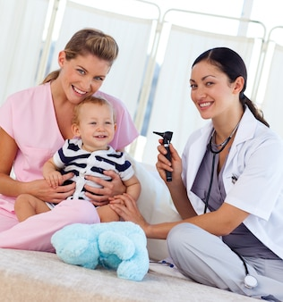 Dziecko z pediatra i pielęgniarka uśmiecha się do kamery