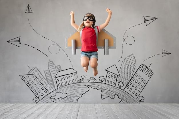Dziecko z plecakiem odrzutowym, skoki przed szarej betonowej ścianie.
