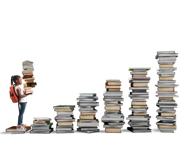 Dziecko z plecakiem wspina się na skalę książek