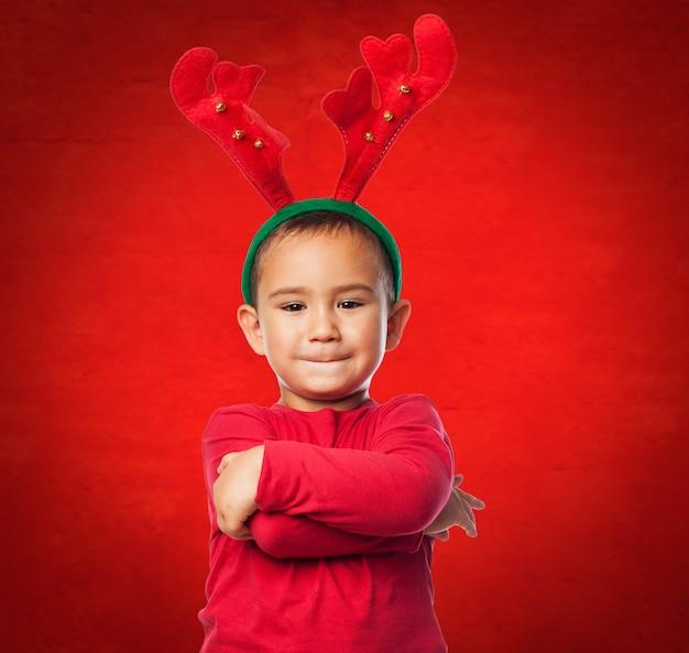 Dziecko z pluszowych poroża reniferów w czerwonym tle
