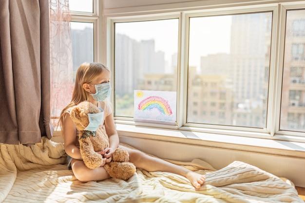 Dziecko z pomalowaną tęczą podczas kwarantanny covid-19 w domu