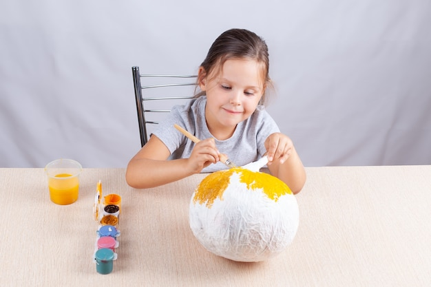 Dziecko z przyjemnością i uśmiechem ozdabia domowej roboty dynię na halloween, przygotowując się do wakacji w odosobnieniu