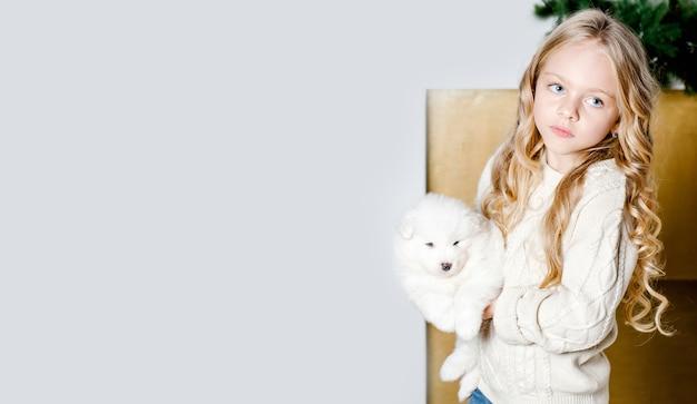 Dziecko z psem szczeniakiem samoyed