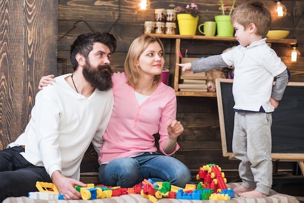 Dziecko z rodzicami bawiące się konstrukcją rodzice przytulają się obserwując bawiącego się syna radość z rodzicielstwa ojciec matka i syn bawią się klockami konstruktora koncepcja rodzicielstwa