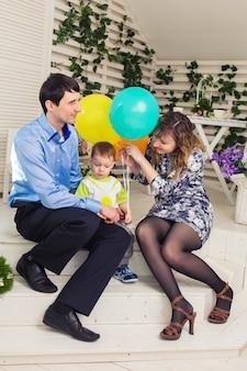 Dziecko z rodzicami z okazji urodzin. szczęśliwa rodzina razem świętuje dzień urodzin.