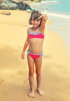 Dziecko z rozgwiazdą w rękach na plaży