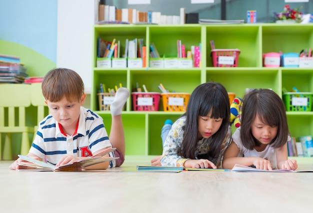 Dziecko z różnorodności układa się na podłodze i czyta książkę z bajkami w bibliotece przedszkolnej