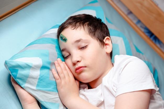 Dziecko z urazem czoła śpi. szew chirurgiczny na czole