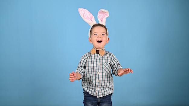 Dziecko z uszami królika, na niebieskim tle. wysokiej jakości zdjęcie