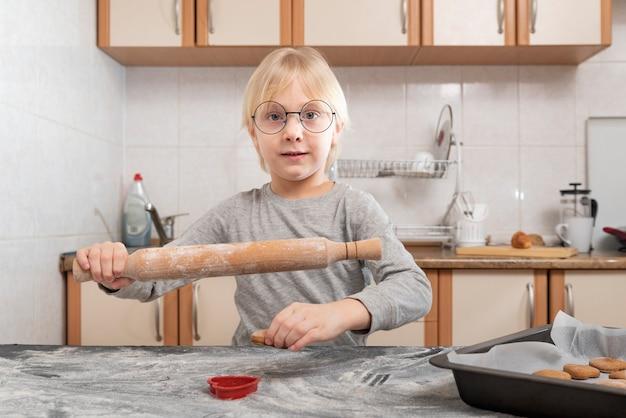 Dziecko z wałkiem w dłoniach rozwałkowuje ciasto