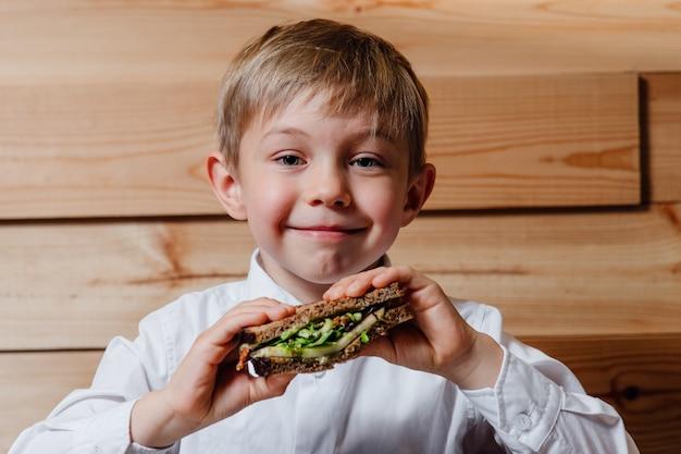 Dziecko z wegetariańską kanapką z chlebem pełnoziarnistym