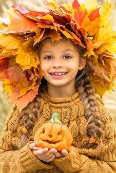Dziecko z wieńcem na głowie i dynią w rękach na halloween.