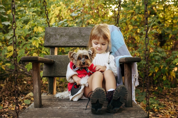 Dziecko z zabawnym psem siedzi w dużym drewnianym krześle w ogrodzie. kobiece dziecko z szczeniakiem pozuje na podwórku. szczęśliwe dzieciństwo