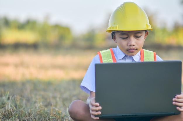 Dziecko z żółtym kask i laptopa