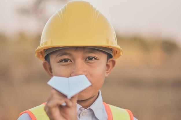 Dziecko z żółtym kask i papierowy samolot