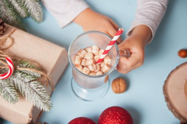 Dziecko za rękę trzyma szklankę kakao boże narodzenie z pianki.